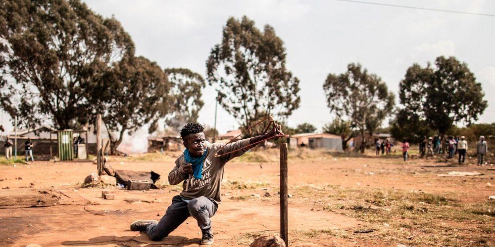 Человек с рогаткой во время протеста в Йоханнесбурге. Фото.